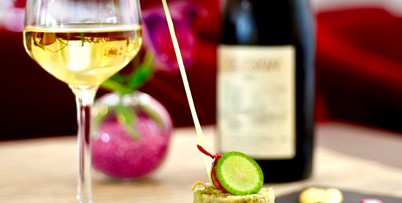A glass of white wine, its bottle and an appetizer on a table