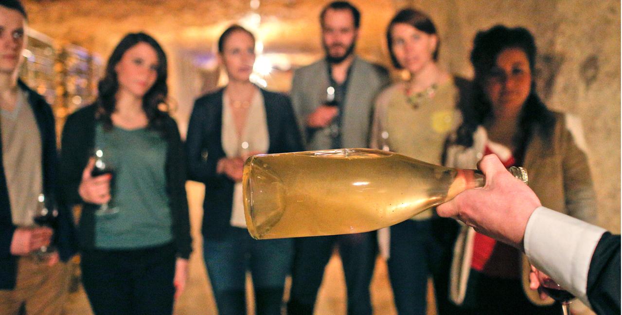 Dégustation dans une cave autour d'une bouteille de vin blanc